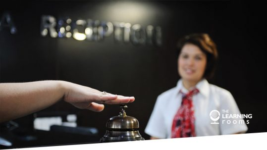 Guest rings bell at hotel reception desk